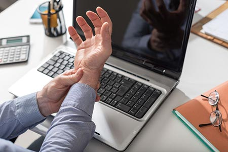 man at a laptop computer suffering from Carpal Tunnel Syndrome